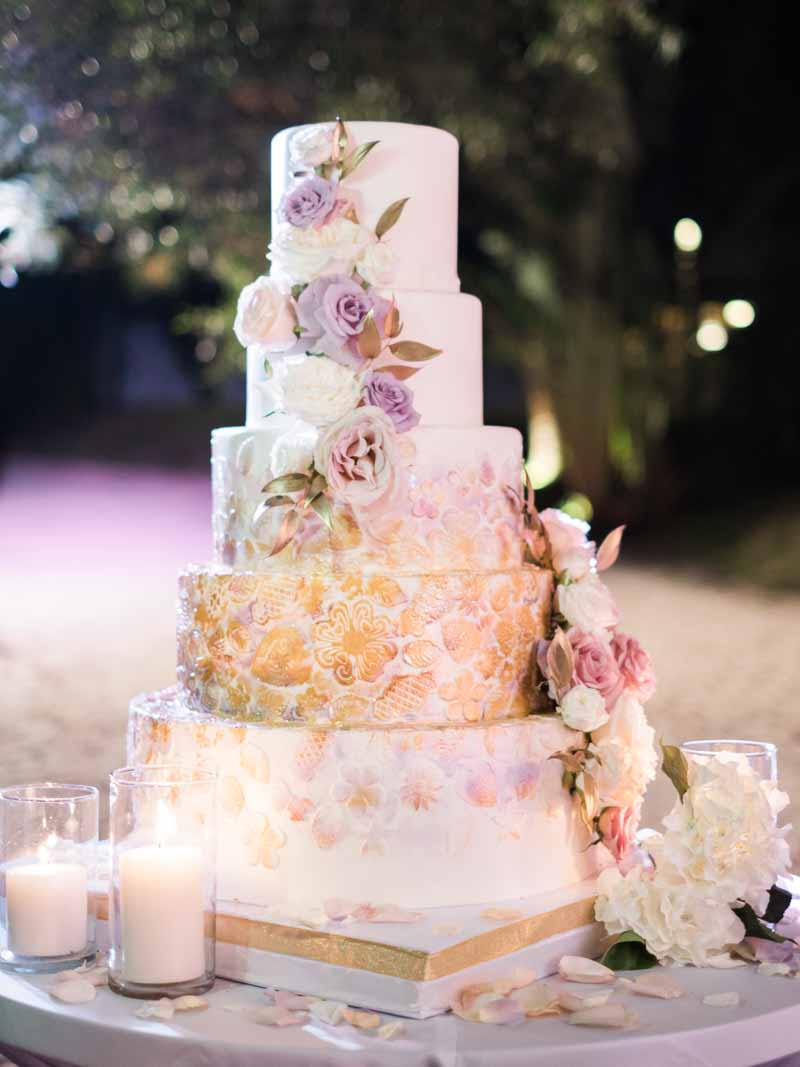 A 5 tier wedding cake with lavender florals and stunning gold patterns, this is what we call a wedding cake! #weddingcakewin