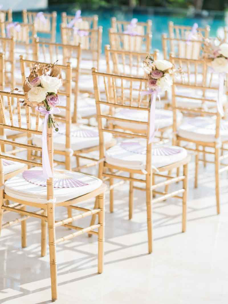 Can't go wrong with gold tiffany chairs for the guests! We added a lavender fan (it was very hot that day) and florals on the aisle seats to bring life to the whole guest seating area! #everydetailmatters