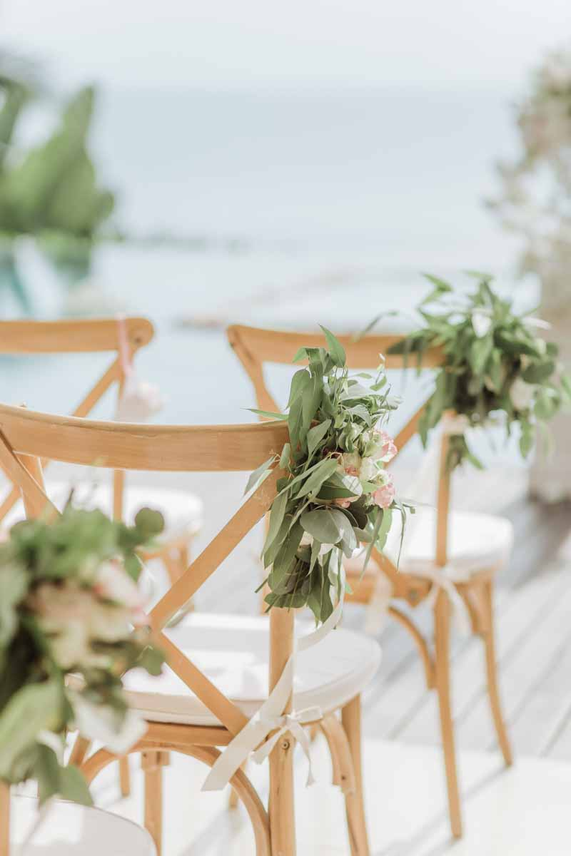 The theme was rustic with lots of greenery. We think these wooden crossback chairs and pretty greenery did the job! #aisleseats