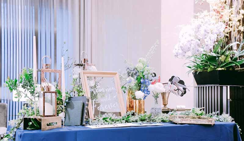 The sign in table for a navy blue themed wedding with lots of greenery. #westernwedding